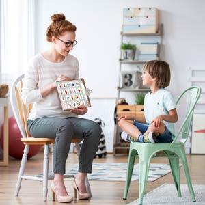 Speech Pathologist and child using PODD